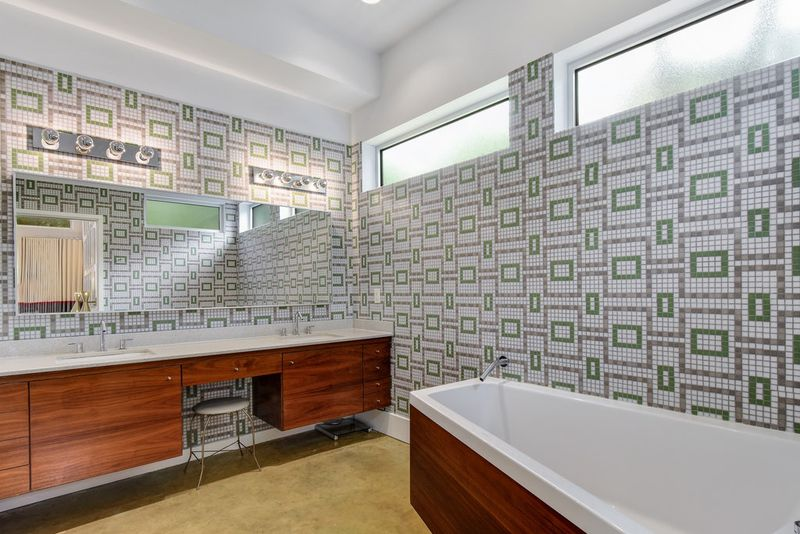 A bathroom with a green and gray geometric tile on the walls, white and wood tub.