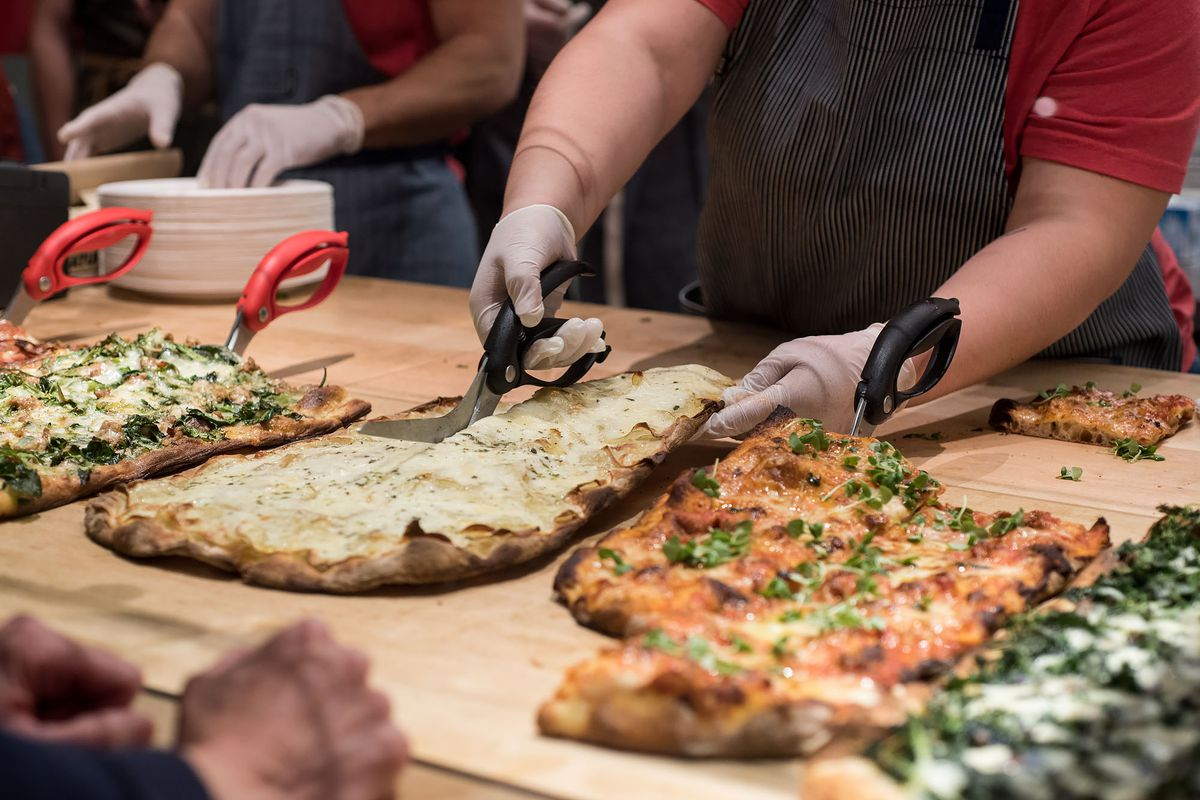 Pizza being cut with scissors because customers can buy pizza by the ounce at Triple Beam.