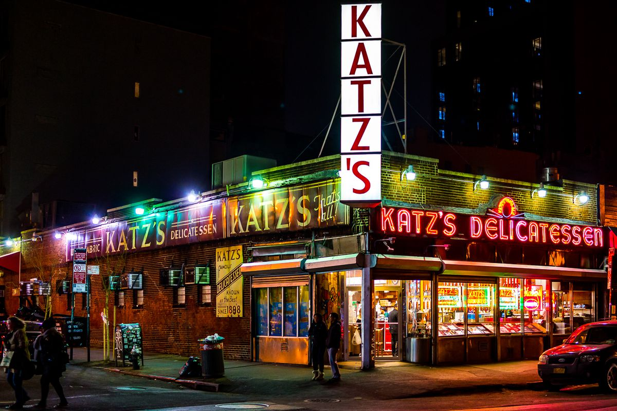 Katz's in 2015 with glowing neon signs on a corner at midnight.