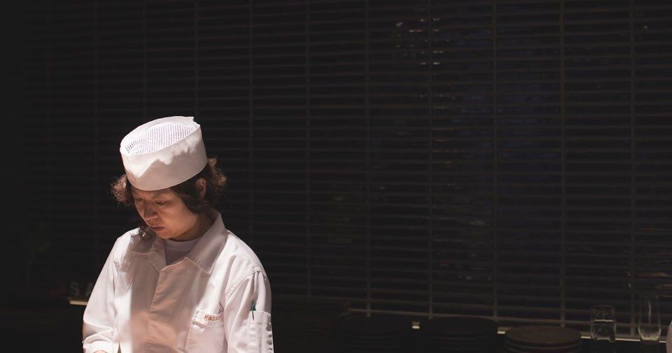 Chef Sho Boo dressed in a white uniform against a dark background