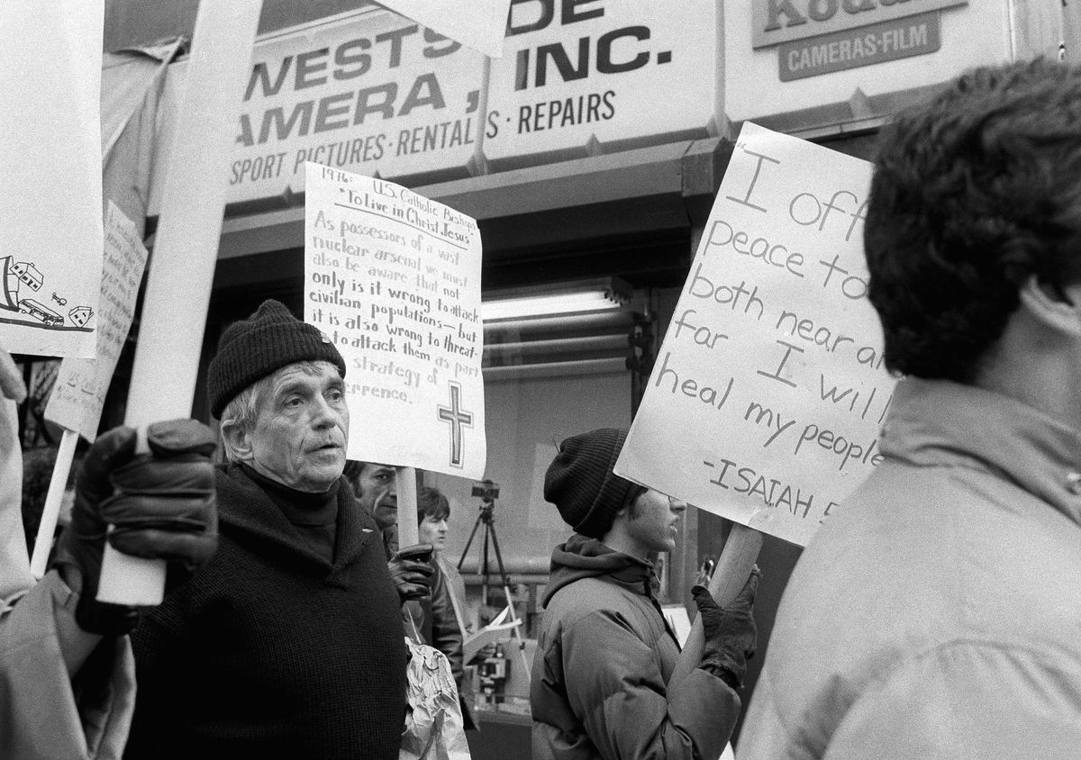 This April 9, 1982, photo shows Daniel Berrigan marching with about 40 others outside the Riverside Research Center in New York. AP file photo