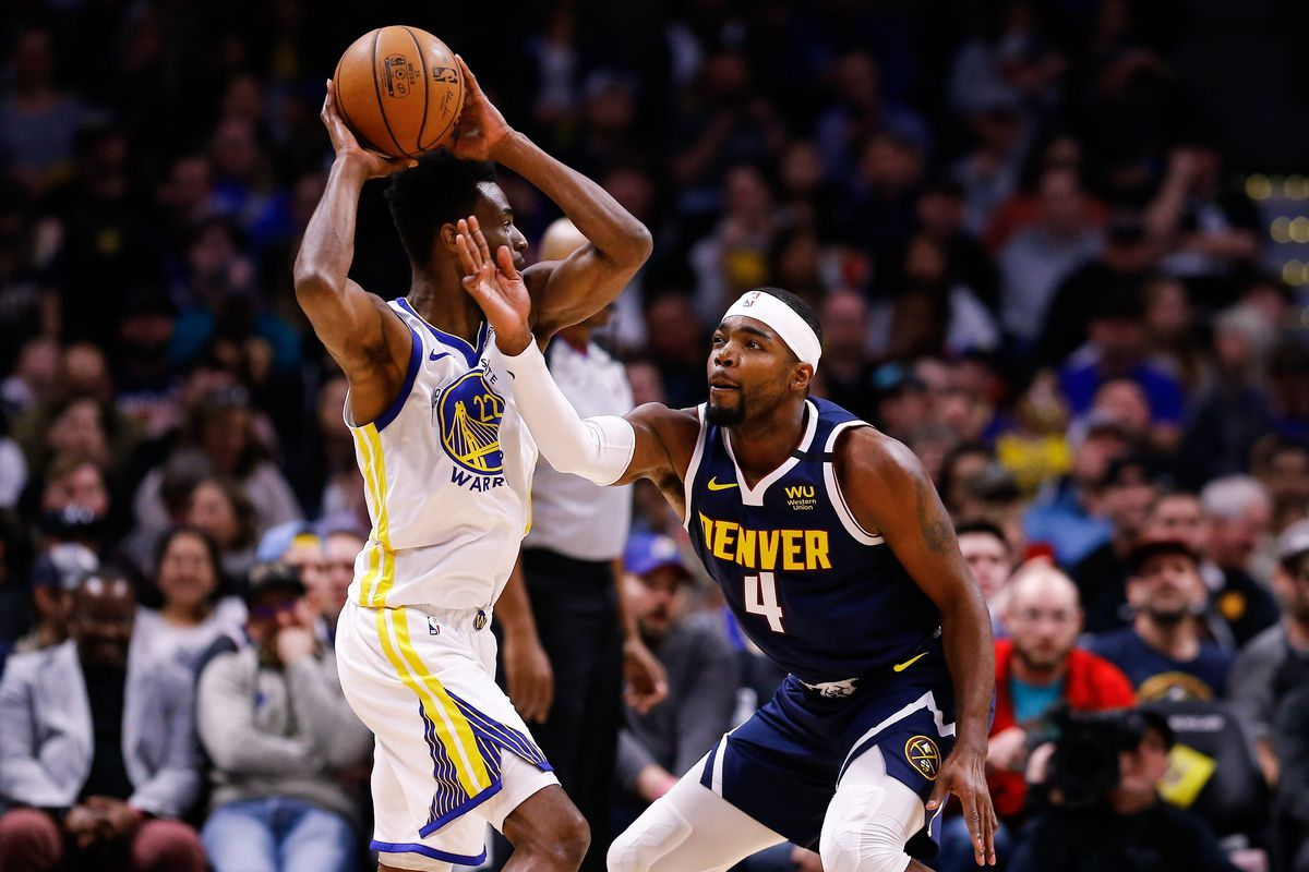 Golden State Warriors guard Andrew Wiggins controls the ball as Denver Nuggets forward Paul Millsap defends in the second quarter at the Pepsi Center.