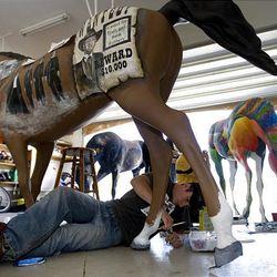 Michael Collins paints a fiberglass horses for Ogden Pioneer Days.