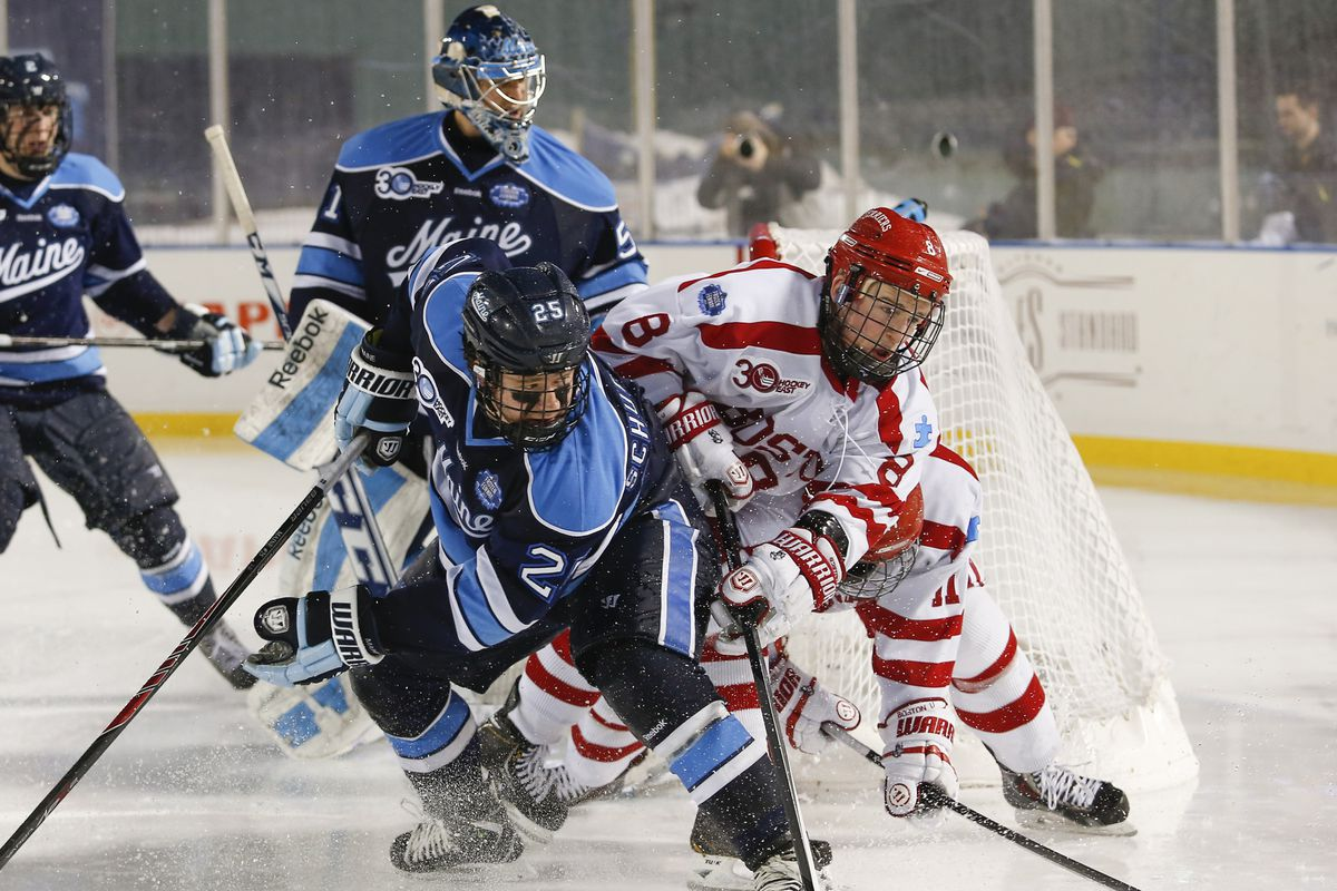 Brendan Collier (right) fights for the puck with Maine players at the 2014 Frozen Fenway, a 7-3 loss for the Terriers.