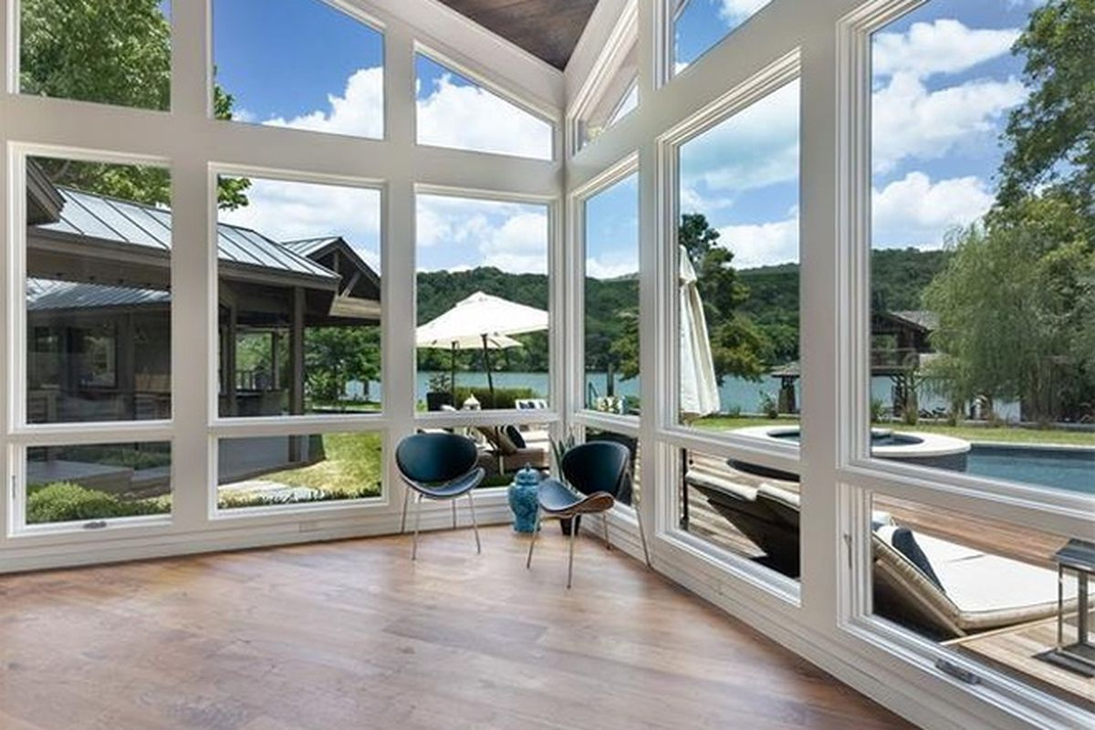 Two-story residential space with angled windows, wood floors and ceilings, angled ceilings, deck and lake outside