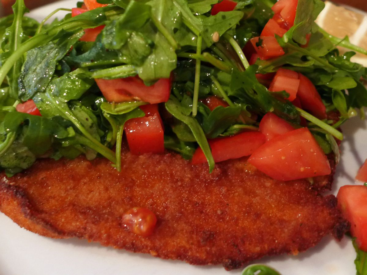 A crumbed and browned chicken cutlet under a nest of arugula and tomatoes.