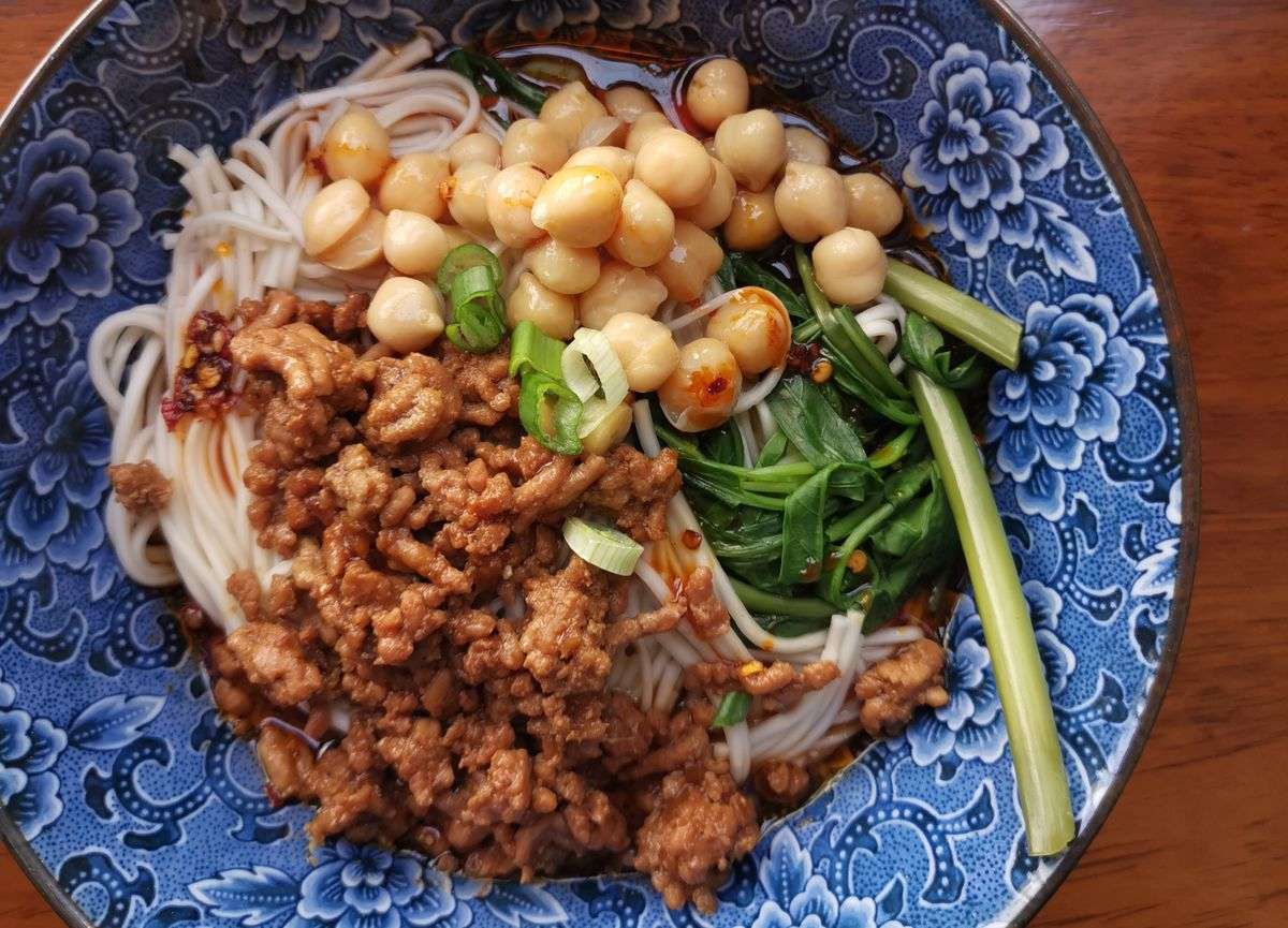 Chongqing noodles with minced pork and chickpeas in a blue bowl