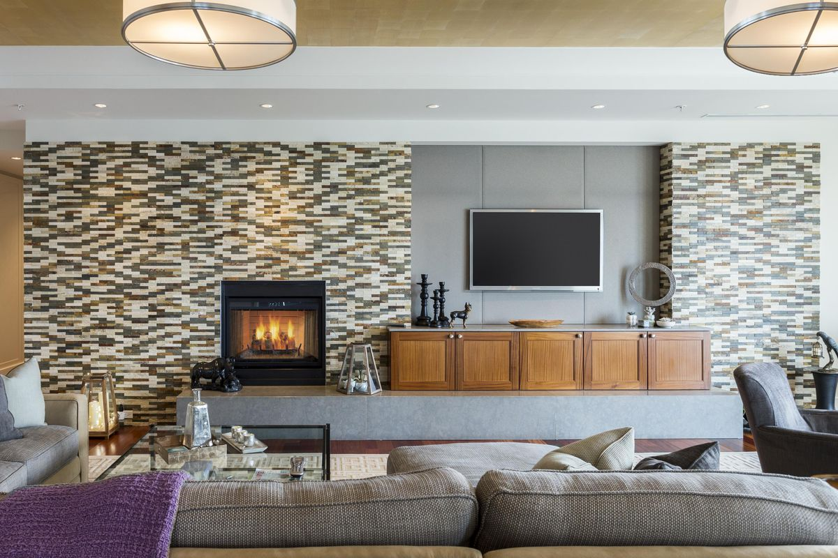 A modern living room with a flat-screen TV on the wall next to a fireplace.