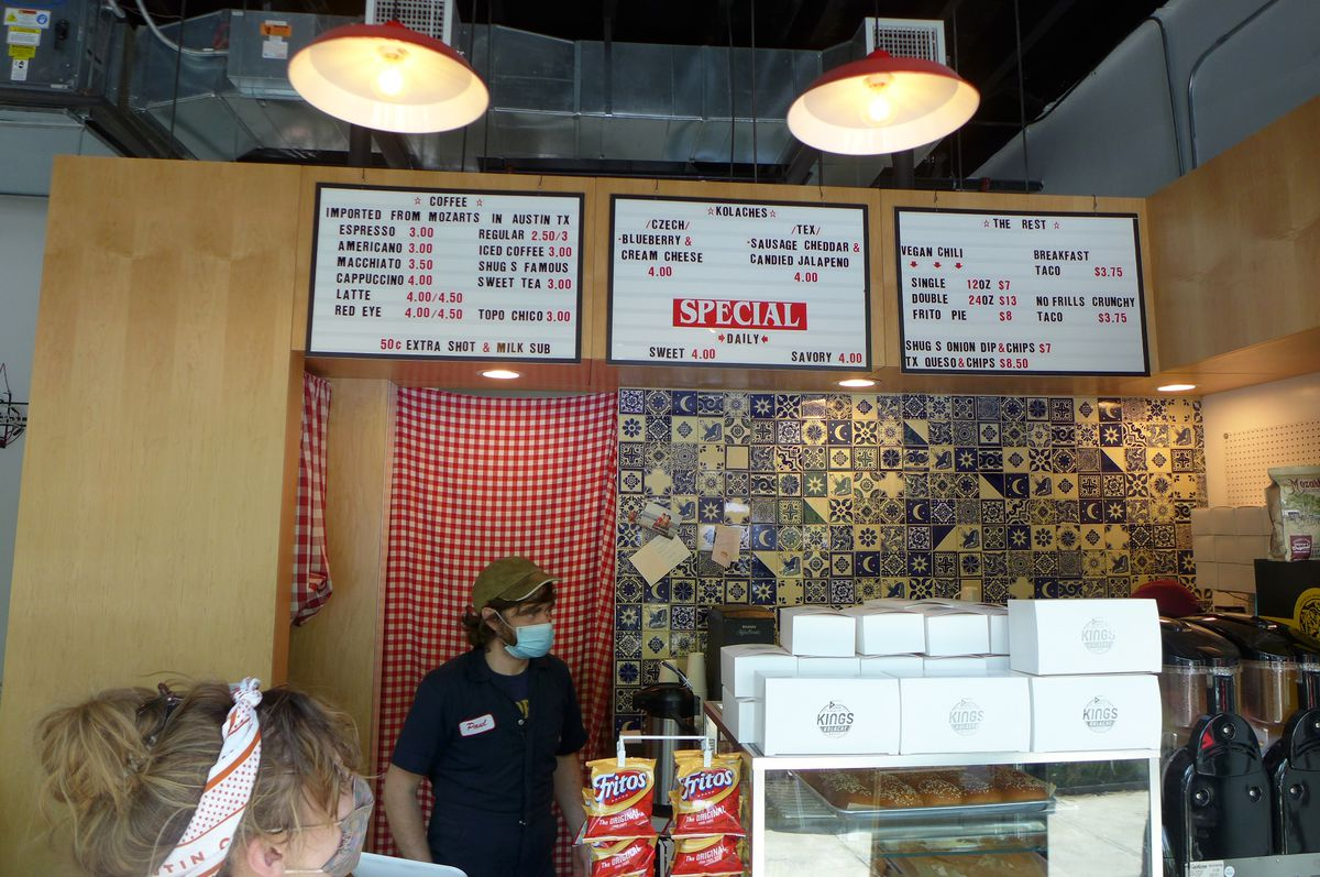 A rustic interior with a backlit signboard and an attendante behind the counter in a baseball cap.