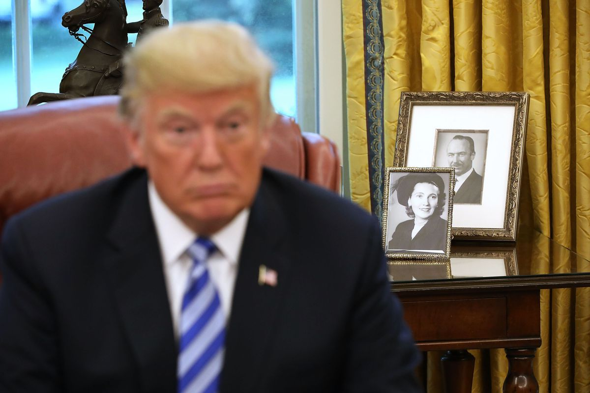 Framed photos of President Donald Trump's parents, Fred and Mary Trump, in the Oval Office.