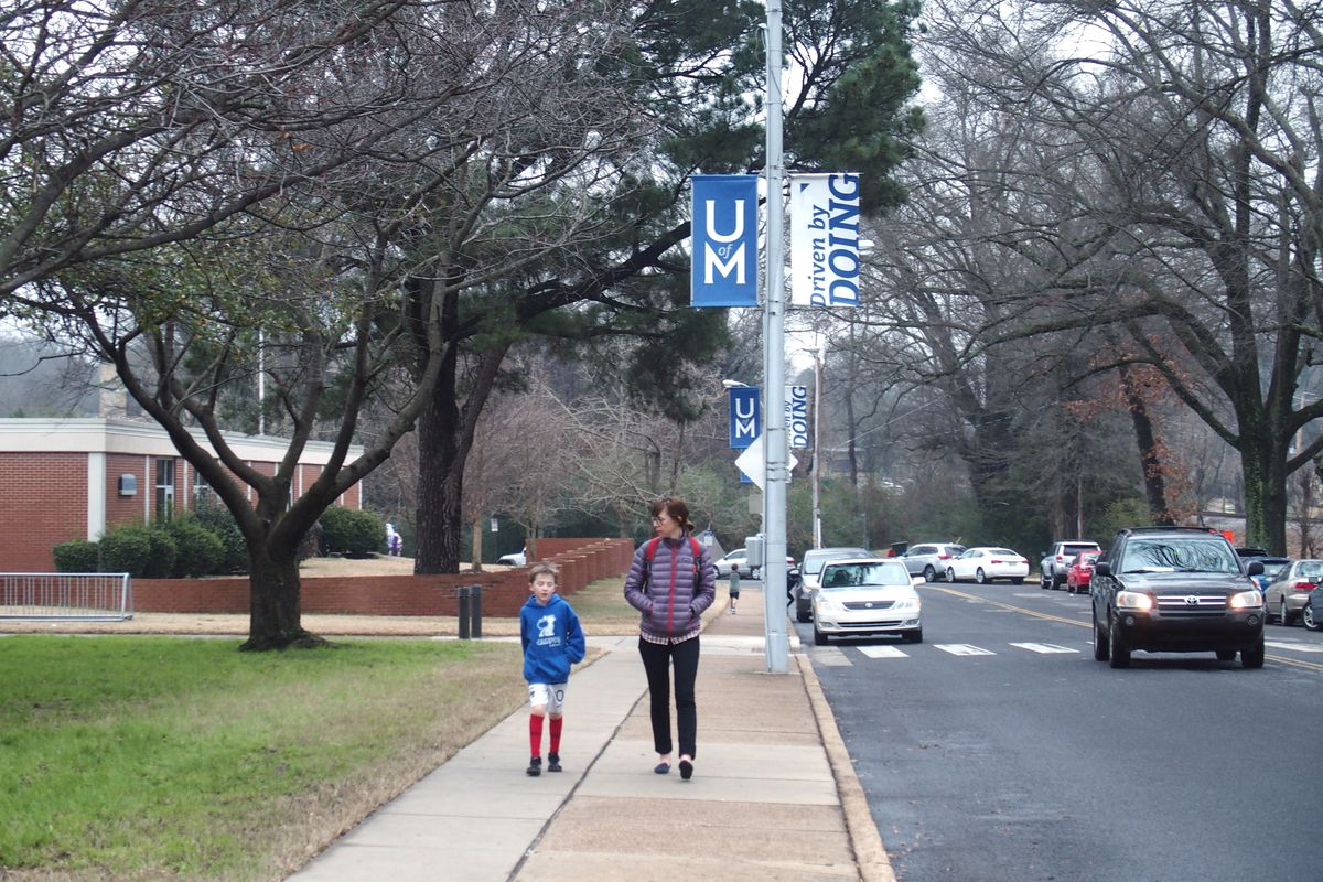 A young student walks with another person outside a school.