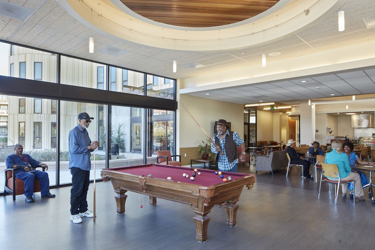 A community room with a billiards table, a cafe, and floor-to-ceiling windows. People are playing pool and sitting at tables in the cafe.