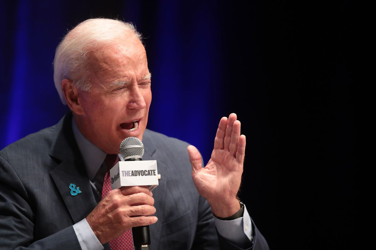 Biden gestures while wearing a suit with a GLAAD pin in the buttonhole.