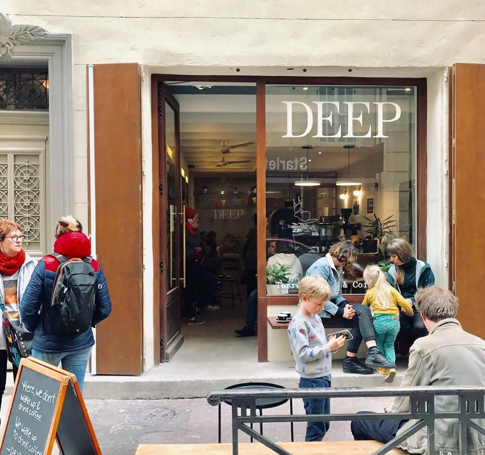 A cafe storefront with the name DEEP in big letters across the top of the window, and customers gathered outside and in