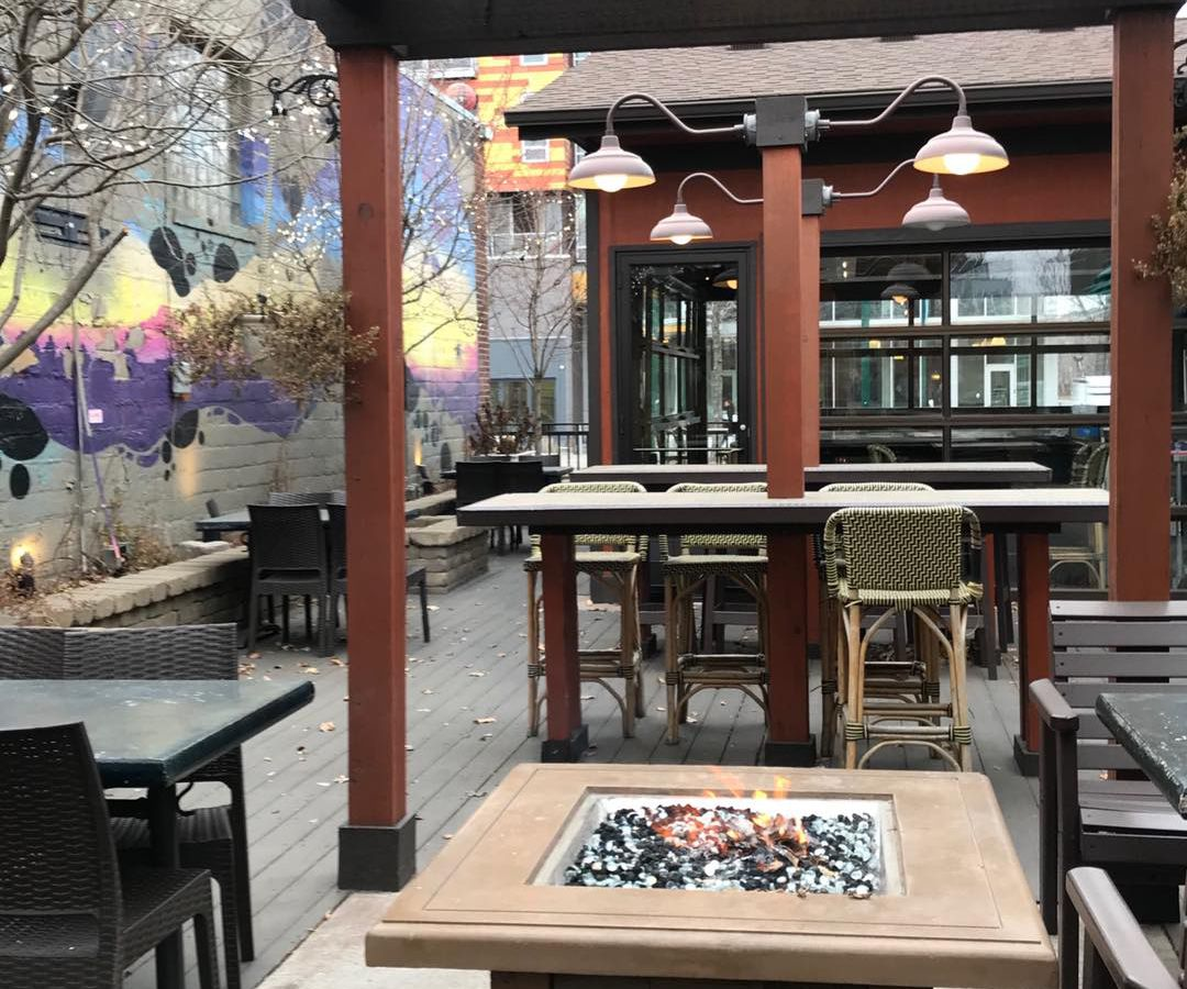The Uptown patio with space tables set apart and a small gas firepit in the center