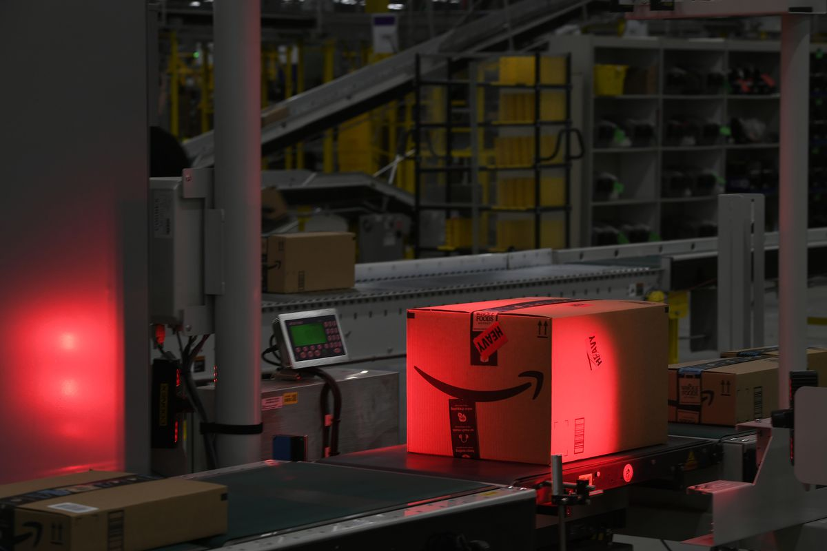 An Amazon box slides down a conveyor belt and gets scanned under a red light.