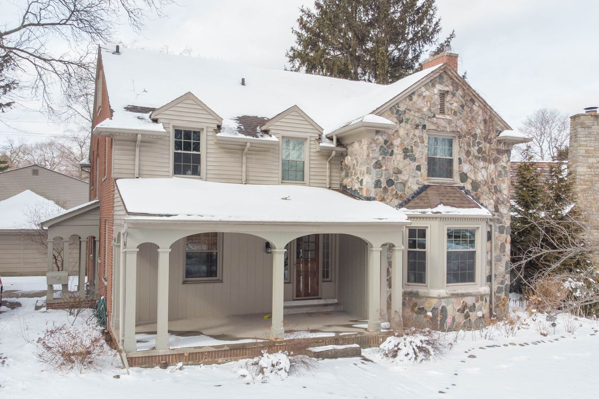 A two story home with a wide front porch and bay window. There's cream-colored vinyl siding and stone siding. Snow covers the ground and roof.