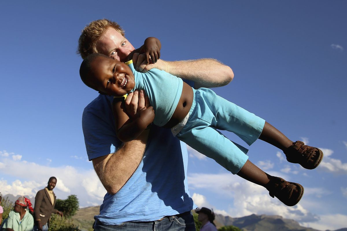In this file photo taken on Dec. 6 2014, Britain's Prince Harry swings young 3-year-old orphan boy Lerato in this photograph taken with the help of a 3-year-old blind girl called Karabo during a visit to Phelisanong Children's Home in Maseru, Lesotho.