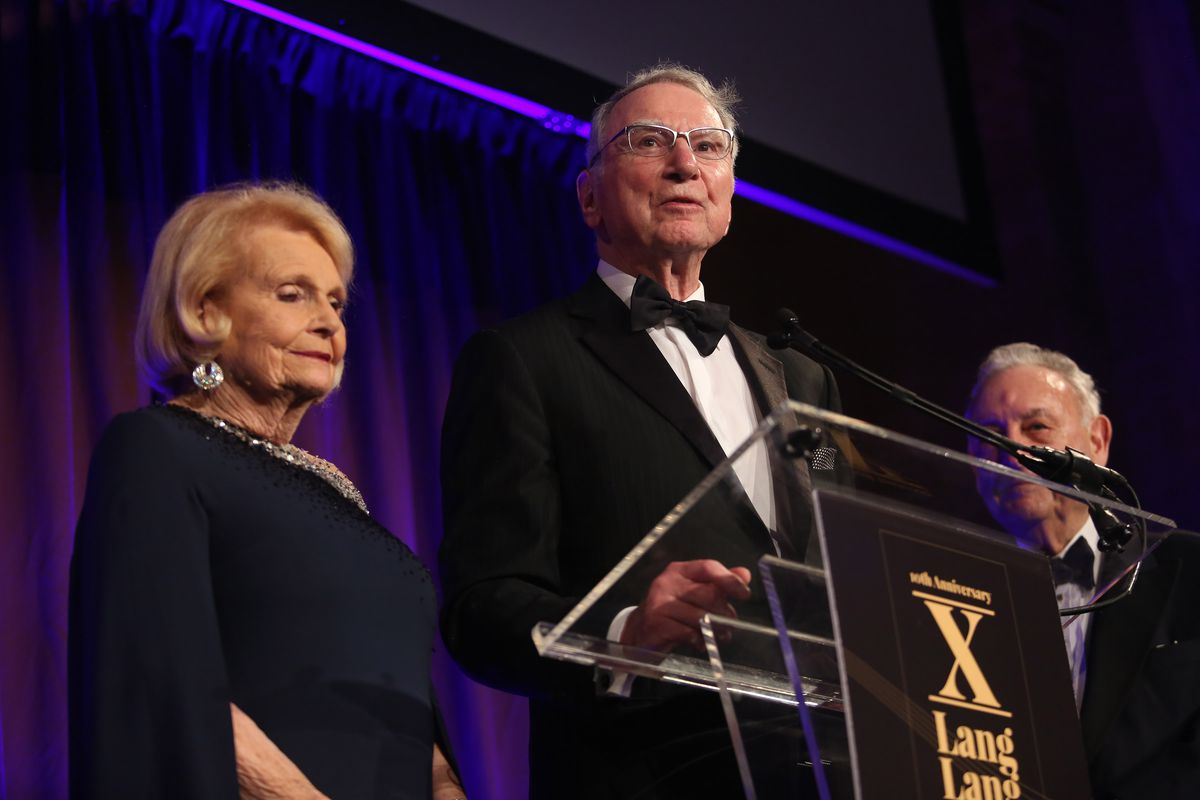 Qualcomm founder Irwin Jacobs speaking onstage from behind a podium with his wife standing next to him.