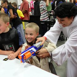 From left, Harper Brace, as Darth Vader, Collier Brace, as Yoda, and Heather Brace, as Princess Leia, play Blast-A-Trooper at Comic Con at the Salt Palace Convention Center in Salt Lake City on Saturday, Sept. 7, 2013.