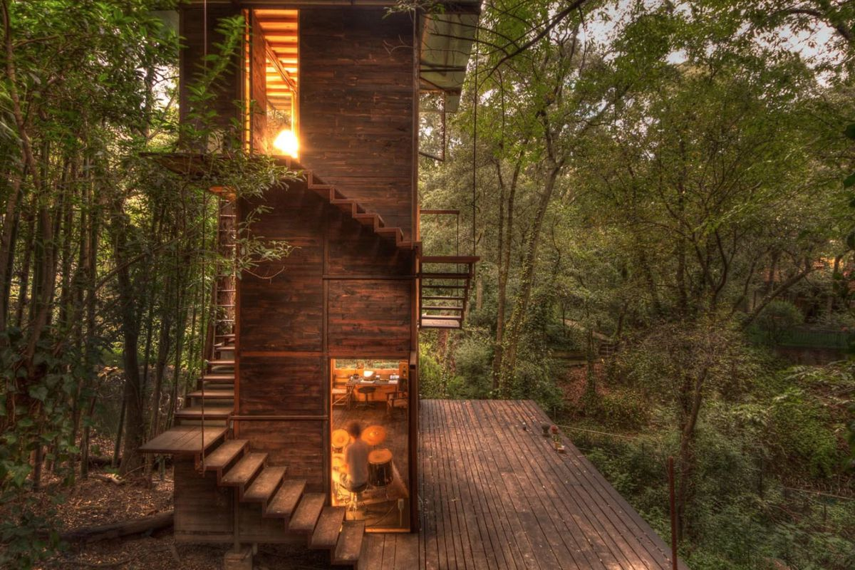 A tree house made of timber in a forest. The house has a staircase and tall windows.