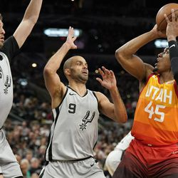 Utah Jazz's Donovan Mitchell (45) attempts to shoot against San Antonio Spurs' Pau Gasol (16) and Tony Parker during the second half of an NBA basketball game Friday, March 23, 2018, in San Antonio. San Antonio won 124-120 in overtime. (AP Photo/Darren Abate)