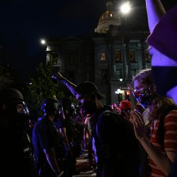 Demonstrators protesting the death of George Floyd at the hands of Minneapolis police face off with Denver Police officers outside the Colorado Capitol.