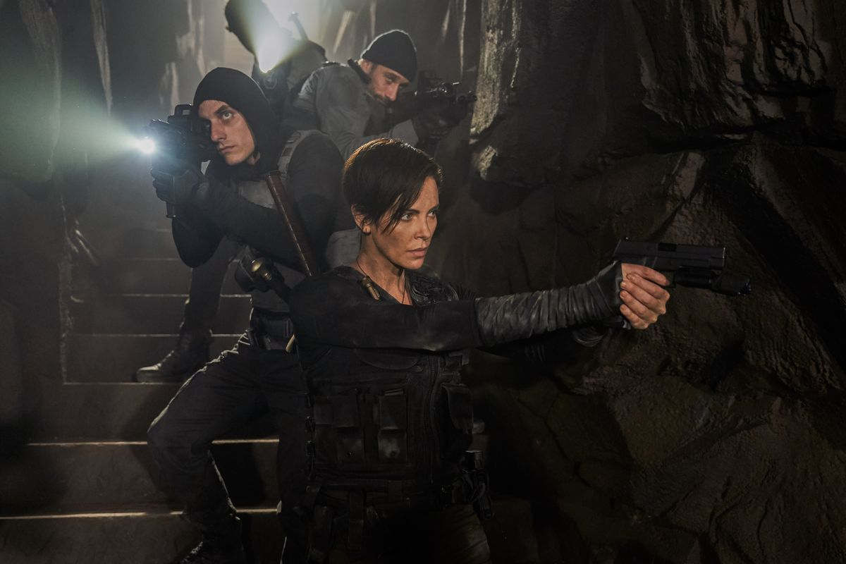Charlize Theron leads her team down into a dark underground area in The Old Guard.