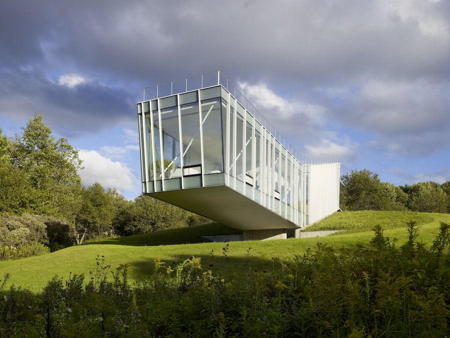 A glassy, bridge-like building that sticks off a hill.