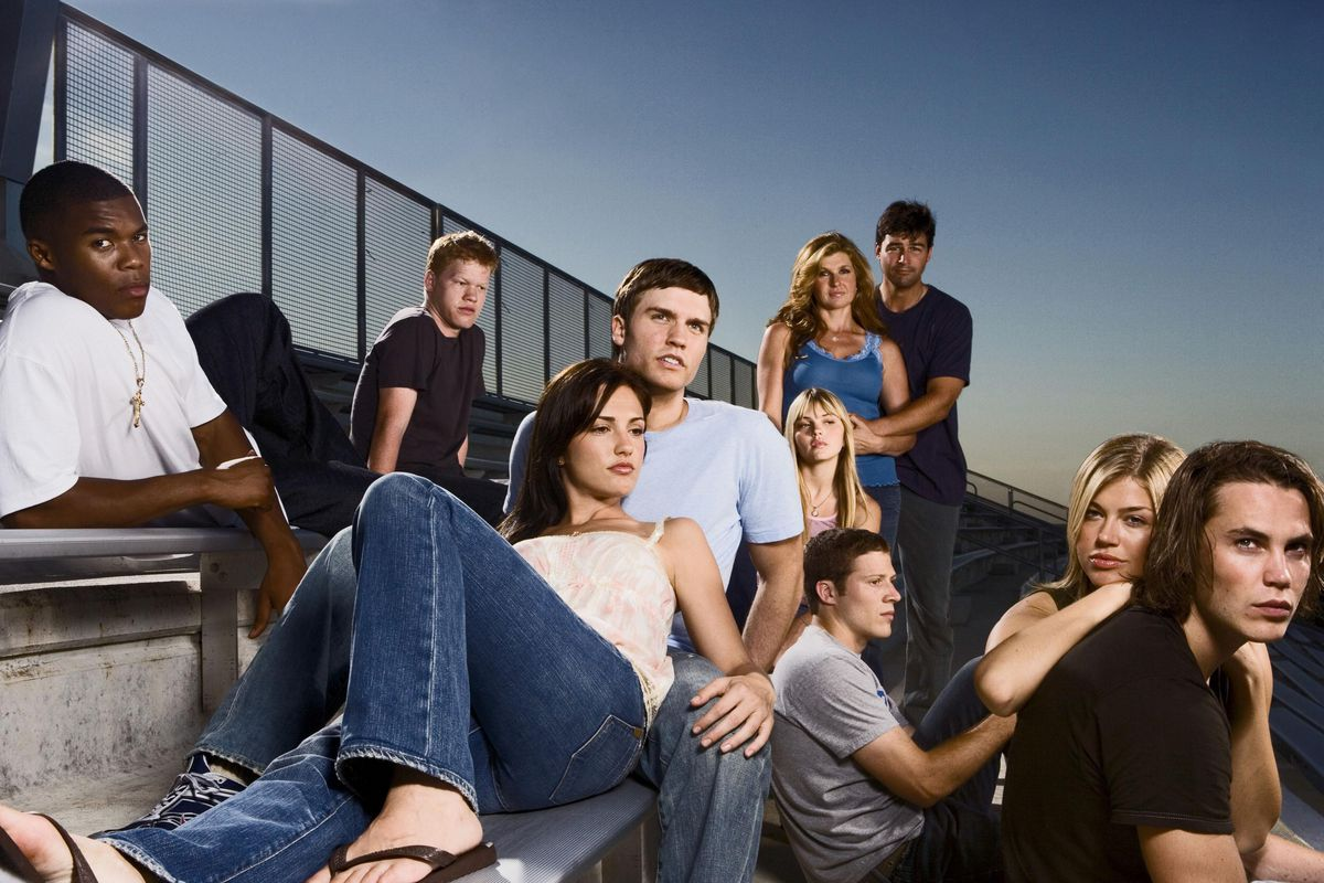 The cast of 'Friday Night Lights' sitting on the bleachers