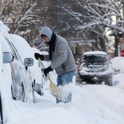A person uses a broom to dig dig his car out the snow in the Edgewater neighborhood, Tuesday morning, Feb. 16, 2021, after a snowstorm dumped over a foot of snow in Chicago starting Sunday night. Snow is expected to continue to fall until Tuesday night.