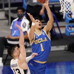 UCLA guard Jules Bernard (1) takes a shot over BYU guard Alex Barcello (13) during the second half of a first-round game in the NCAA college basketball tournament at Hinkle Fieldhouse in Indianapolis, Saturday, March 20, 2021.