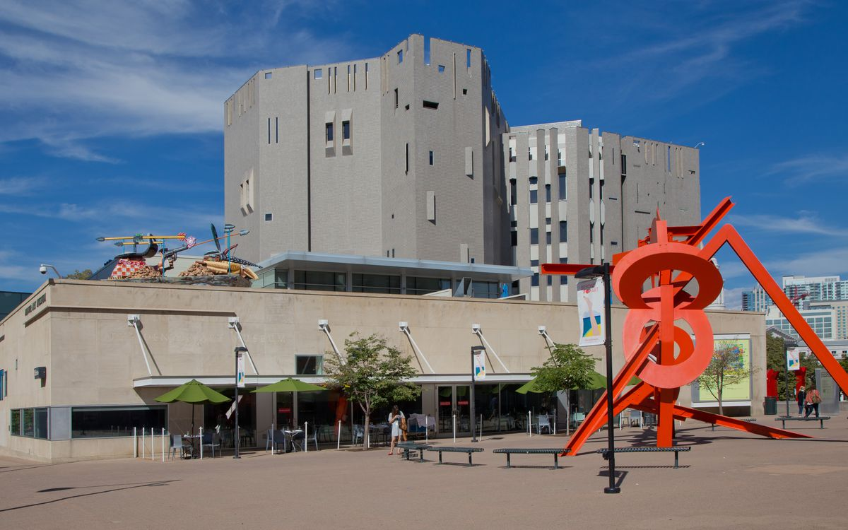 The exterior of the Denver Art Museum in Colorado. The facade consists of reflective glass tiles. There is a bright red sculpture in a courtyard in front of the building.