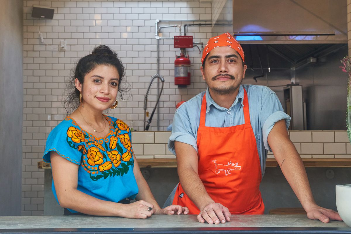 Two people stand at a counter in front of a kitchen, one wearing a bright blue shirt and the other wearing a light blue shirt with an orange apron