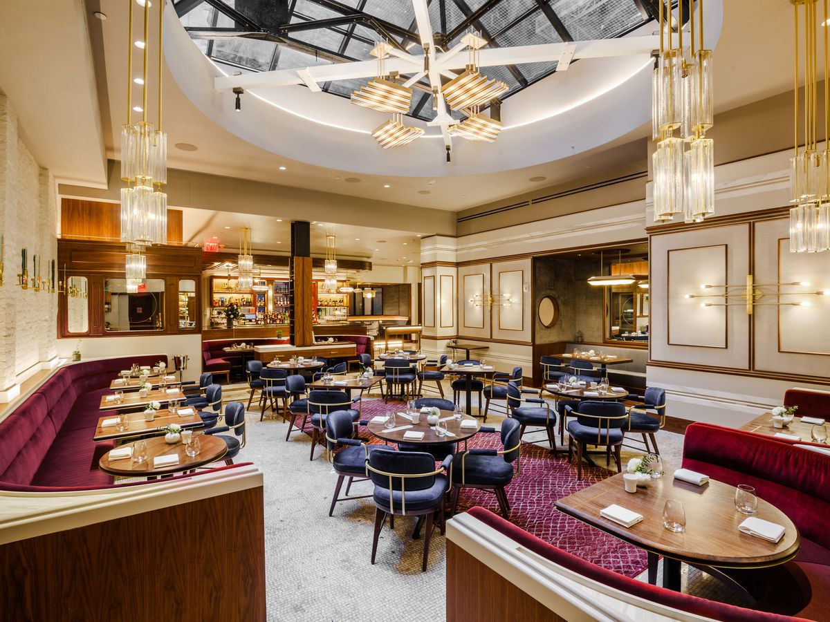 The high-ceilinged dining room with red banquet booths and gold decor at Benno
