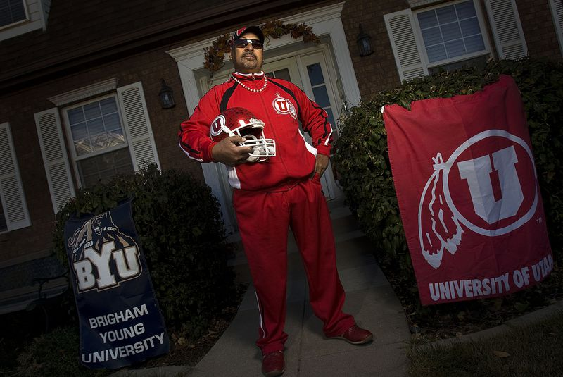 Tom Sitake, a die-hard BYU fan has a son, Kilani coaching on Utah's football staff. He has torn loyalties as a father who has had two sons play for BYU but his oldest is collecting a check from Utah. Wearing a U of U apparel he poses in front of his house in Orem, Utah Saturday Nov. 14, 2008. August MIller/ Deseret News