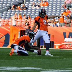 Broncos K Brandon McManus prepares to kick before game time while P Marquette King holds.