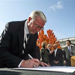 Mark Willes of Deseret Management Corporation signs a document called the Utah Compact in support of immigration reform at the State Capitol in Salt Lake City Thursday.