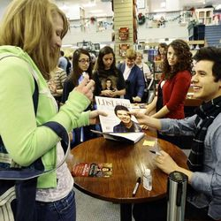 David Archuleta, right, signs a magazine for Amanda Prior during a book signing event at the Deseret Book at Ft. Union in Midvale on Nov. 22.