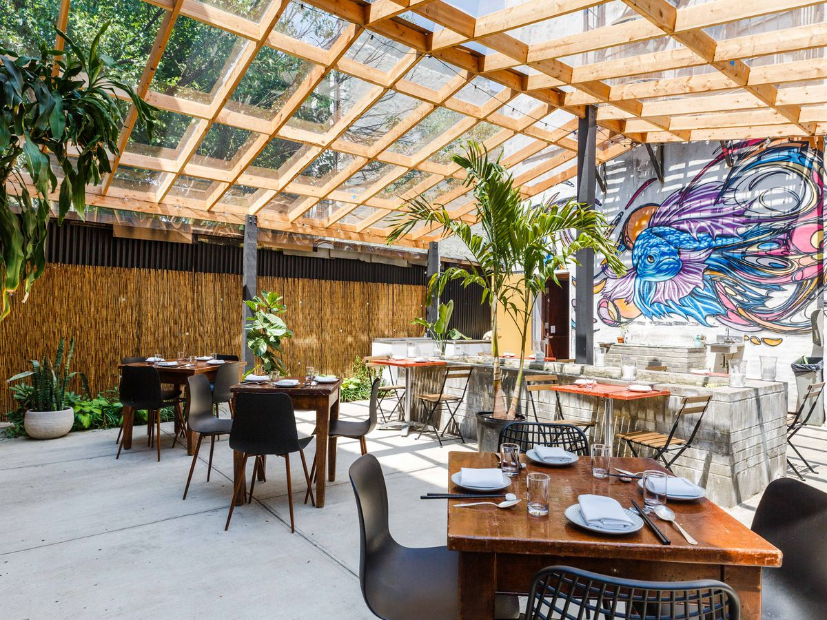 Plants and a mural decorate the outdoor dining area.