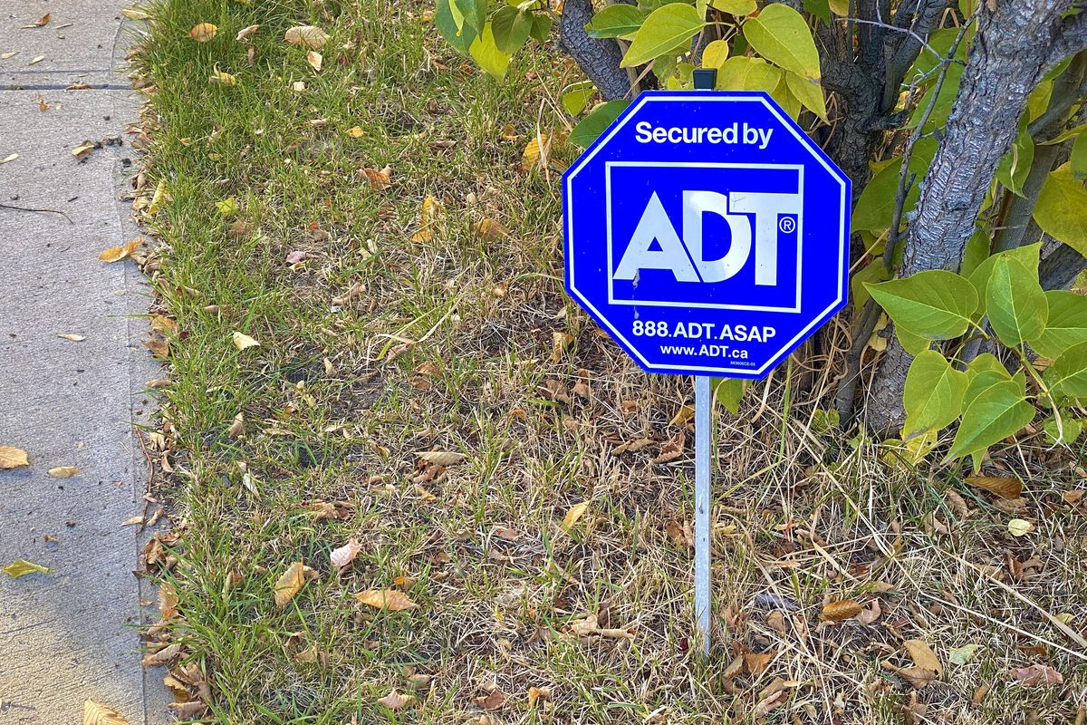 A blue ADT Home Security sign in a yard.