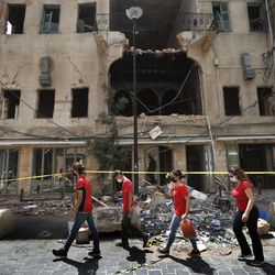 University students who volunteered to help clean damaged homes and give other assistance, pass in front of a building that was damaged by last week's explosion, in Beirut, Lebanon, Tuesday, Aug. 11, 2020. The explosion that tore through Beirut left around a quarter of a million people with homes unfit to live in. But there are no collective shelters, or people sleeping in public parks. That's because in the absence of the state, residents of Beirut opened their homes to relatives, friends and neighbors.