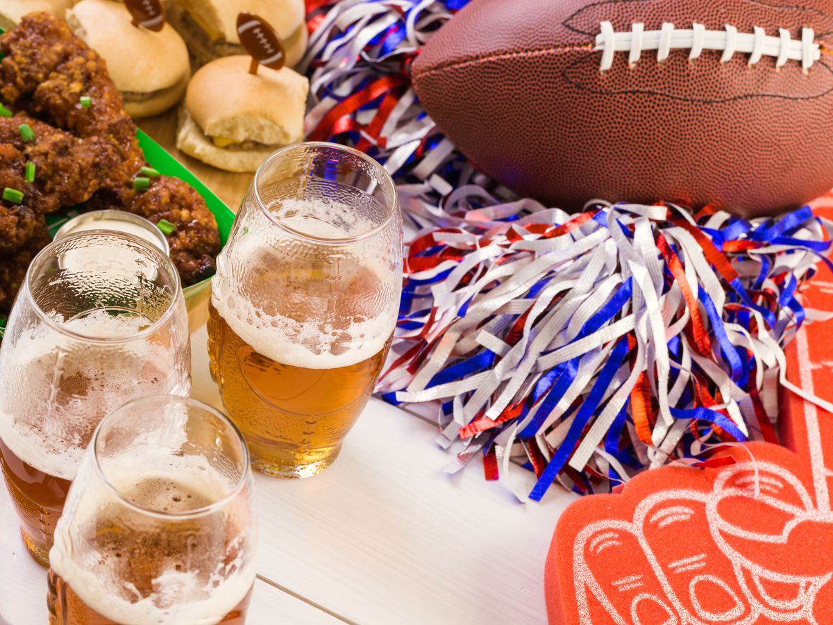 A table with football game day foods like wings, chips, dips, and beer with a football and pom poms