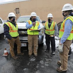 Kylie Hrubes, a Dominion Energy utility worker, Saunjay Hillman, a Dominion Energy lead specialist, Ramone Barrera, a Dominion Energy utility worker, and Joey Stephenson, a Dominion Energy utility worker, go over their plan for replacing a gas meter in West Valley City on Wednesday, Feb. 17, 2021.