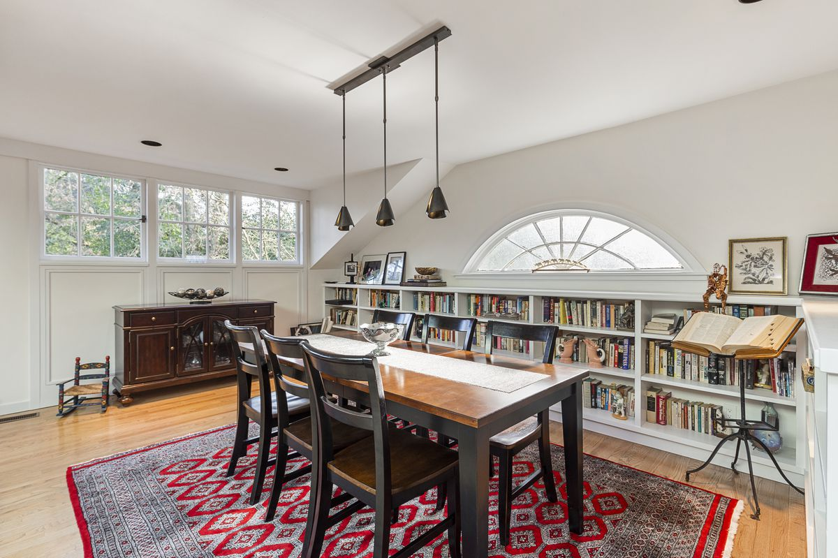A dining room has a patterned rug, seating for six, and built-in bookcases along one wall.