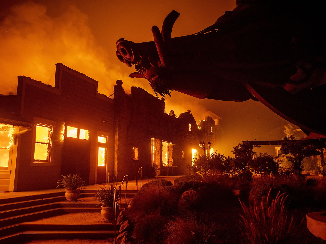 In this Oct. 27, 2019, file photo, flames from the Kincade Fire consume Soda Rock Winery in Healdsburg, Calif. A California prosecutor has charged troubled Pacific Gas & Electric with starting a 2019 wildfire.
