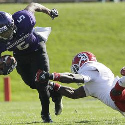 Northwestern running back Venric Mark (5) is tackled by South Dakota defensive back Chris Frierson (7) during the first half of an NCAA college football game in Evanston, Ill., Saturday, Sept. 22, 2012. Northwestern won 38-7.