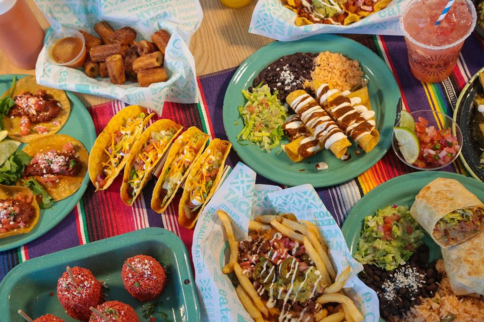 Overhead view of vegan tacos, churros, burritos and beverages