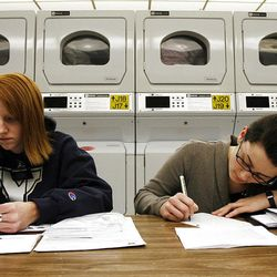 Sister Wendy Evans, left, of Parowan, and Sister Elizabeth  Perkins, of Wasilla, Alaska, write letters while doing laundry.