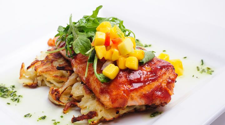 Barbecue salmon on potatoes with a mango chutney on top.